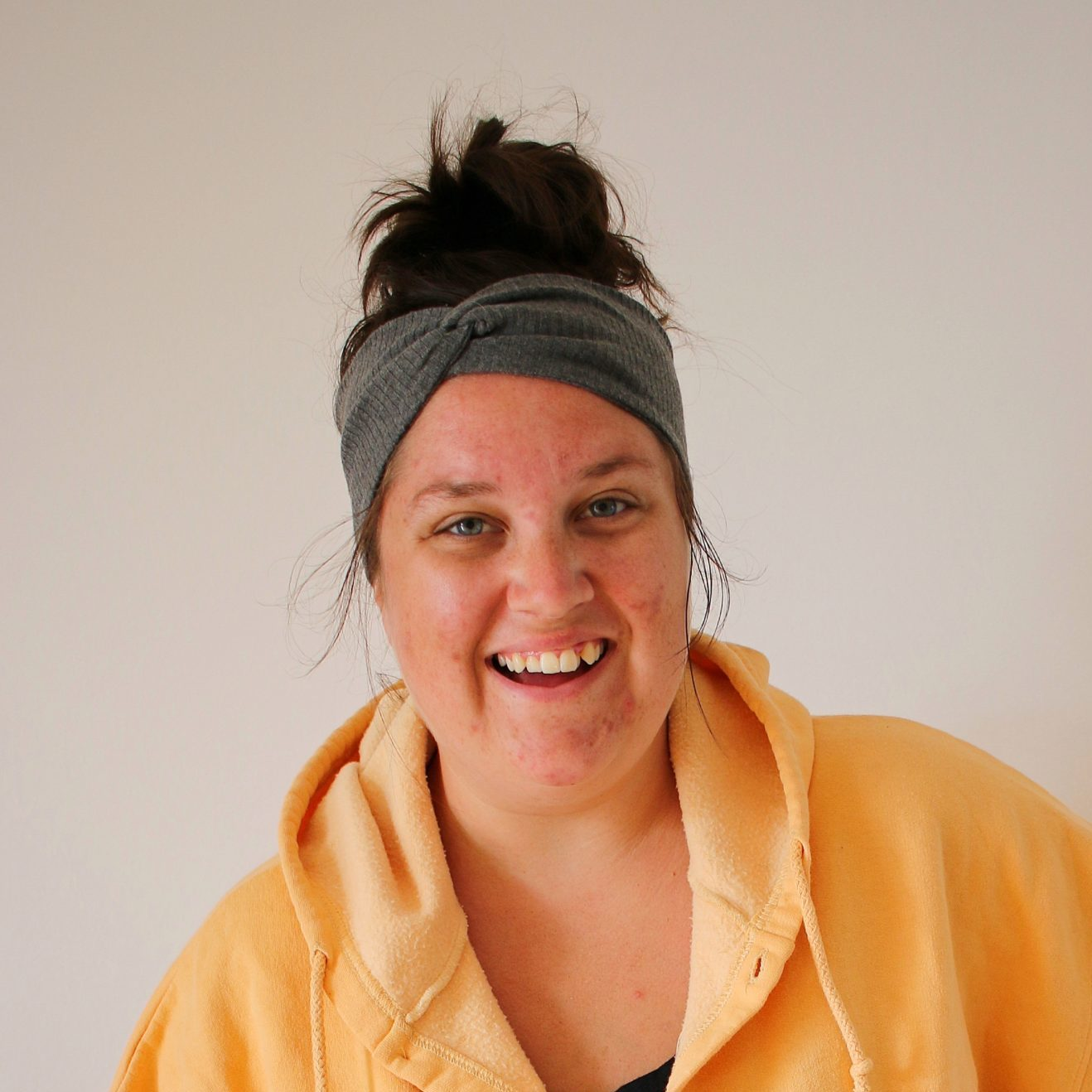 White woman with brown hair up in a bun wearing a grey headband, a golden yellow cropped hoodie and black biker shorts smiles at the camera